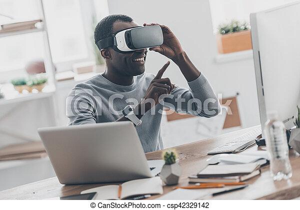 Tecnologías de innovación. Un apuesto joven africano con auriculares de realidad virtual apuntando al aire mientras se sienta en el escritorio en la oficina creativa - csp42329142