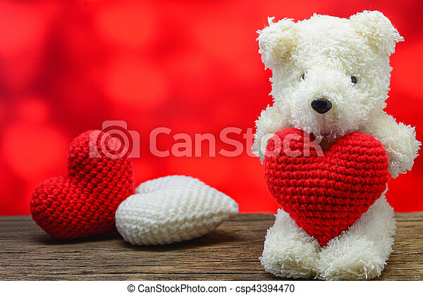 e3078dad Teddy bear holding a heart-shaped on wooden table