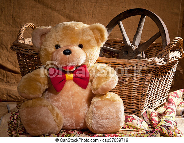 teddy bear is sitting in front of wicker basket - csp37039719
