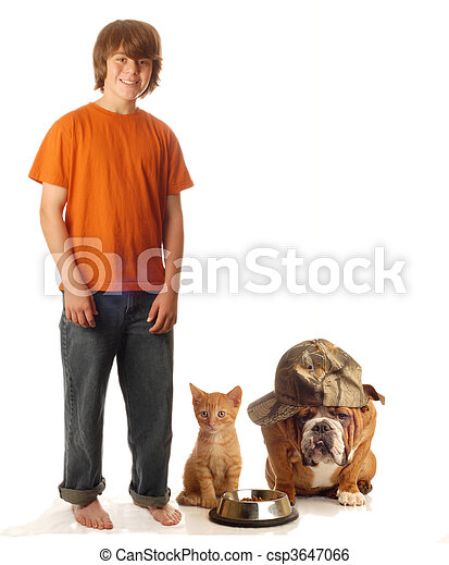 teen boy feeding his dog and cat - csp3647066