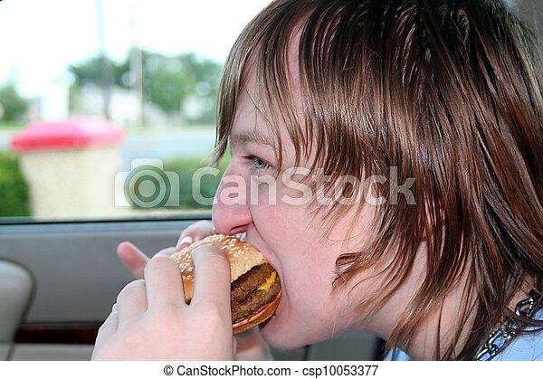 Teen Eating Cheeseburger In Car - csp10053377