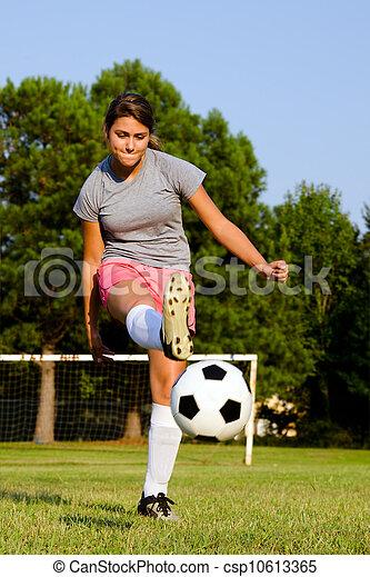 Teen girl kicking soccer ball on field - csp10613365