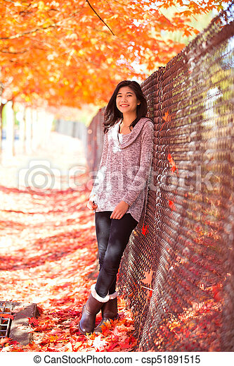Teen Girl Leaning Against Fence Under Canopy Of Maple Trees