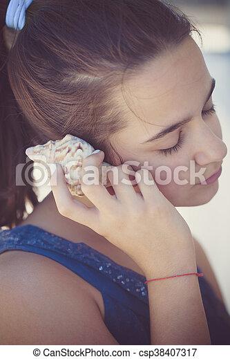 teen girl listen sea shell - csp38407317
