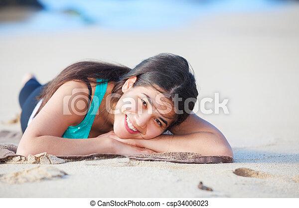 Teen girl lying down on sandy beach, head on arms - csp34006023