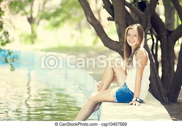 Teen girl near lake in the park. - csp10407569