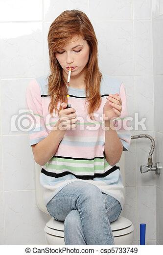Teen girl smoking in - csp5733749