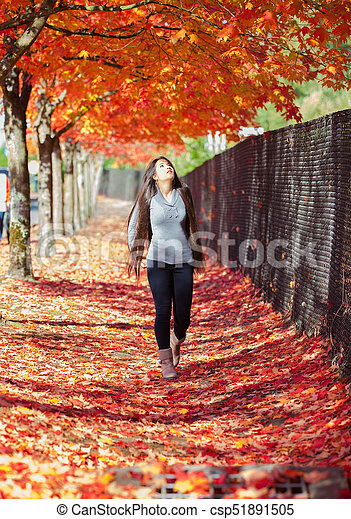 Teen Girl Walking Under Canopy Of Autumn Maple Leaves