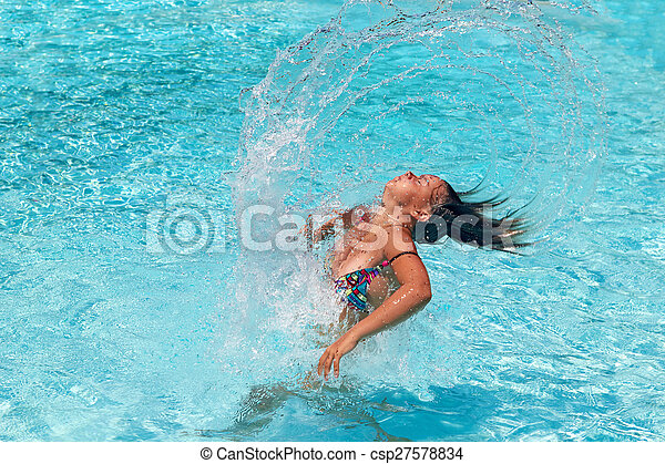 teen girl whipping her hair back in the pool and spraying water everywhere - csp27578834