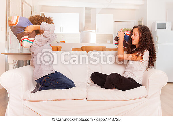 Teenage boy and girl pillow fighting on the couch - csp57743725