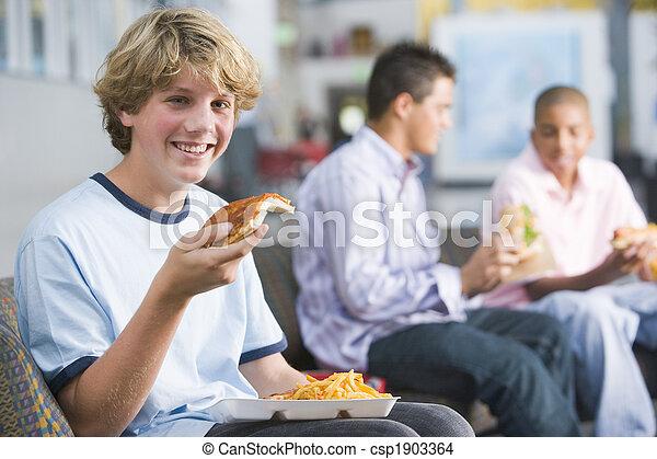 Teenage boys enjoying fast food lunches together - csp1903364