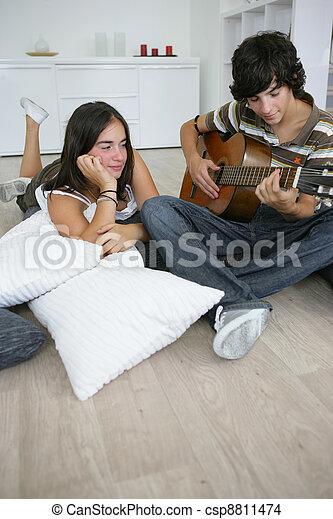 teenage brunette lost in admiration for boyfriend playing guitar - csp8811474