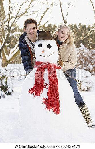 Teenage Couple Building Snowman - csp7429171
