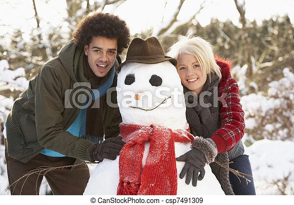 Teenage Couple Building Snowman - csp7491309