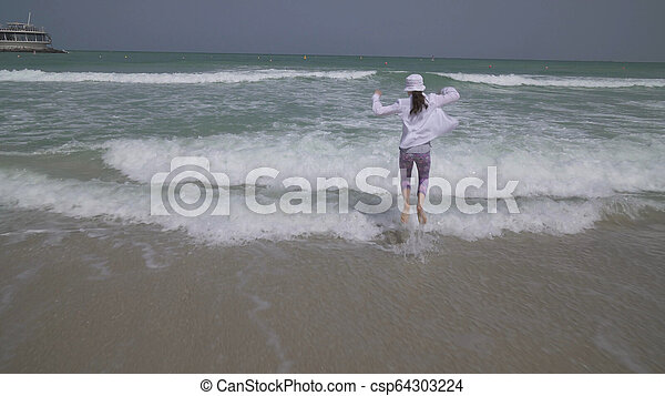 Teenage girl in clothes joyfully jumping in the waves of Persian Gulf on  beach of Dubai