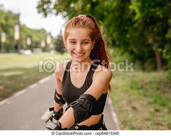 Teenage girl in sportswear roller skating - csp84615345