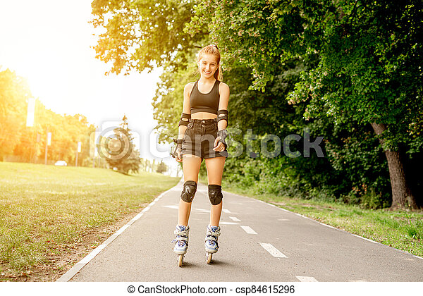 Teenage girl in sportswear roller skating - csp84615296