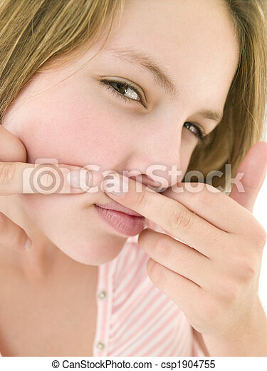 Teenage girl popping zit on face - csp1904755