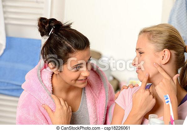 Teenage girls having acne problems in bathroom - csp18226061