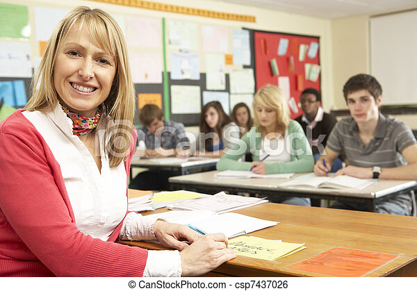 Teenage Students Studying In Classroom With Teacher - csp7437026