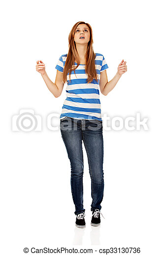 Teenage woman with outstretched arms looking up - csp33130736
