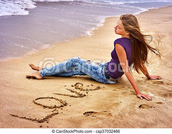 Teenager draw heart on sand on beach sea. - csp37032466