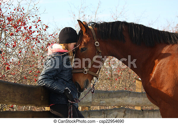 Teenager girl and bay horse hugging each other - csp22954690