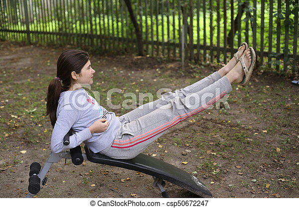 teenager girl work out abs on outdoor trainer csp50672247