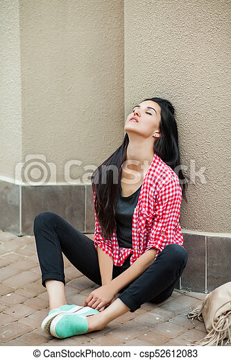 Teenager Sitting On The Ground Leaning Against The Wall