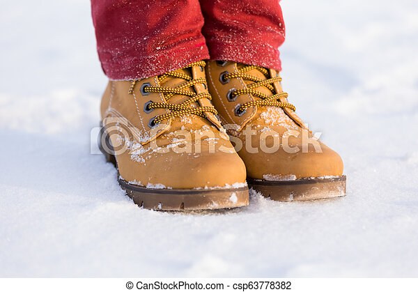Teenager's legs at the yellow boots on the snow - csp63778382