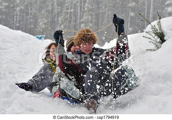 Teens sledding on a saucer - csp1794919