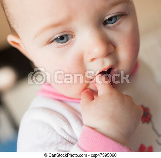 Teething concept. Baby girl with finger in mouth. - csp47395060