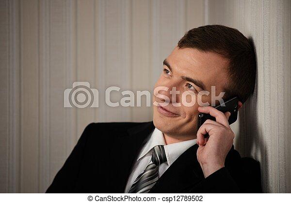 Un hombre guapo con traje negro con el móvil hablando - csp12789502