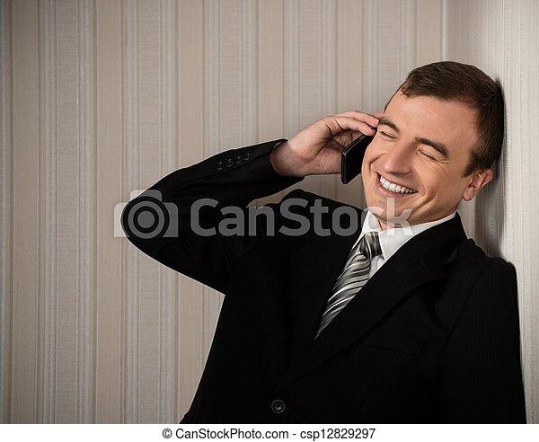 Un hombre guapo con traje negro con el móvil hablando - csp12829297