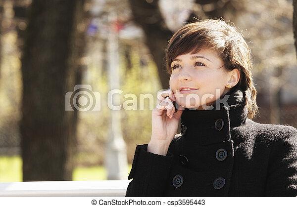 Mujer sonriente en el parque con celular - csp3595443
