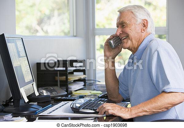 Un hombre en la oficina central por teléfono usando una computadora sonriendo - csp1903698