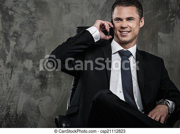 Hombre bien vestido con traje negro con teléfono móvil - csp21112823