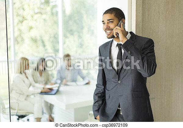 Hombre de negocios en un teléfono en la oficina - csp36972109
