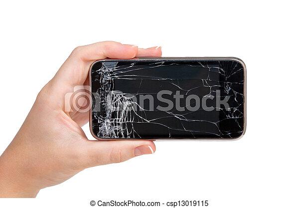 Un teléfono roto en una mano de mujer - csp13019115