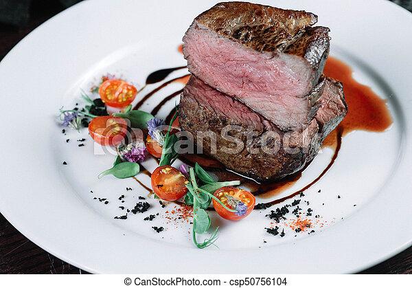 Tenderloin steak on plate with salad on dark background - csp50756104