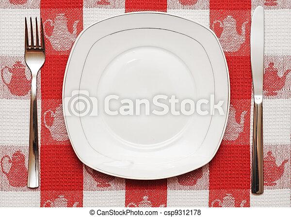 Cuchillo, plato blanco y tenedor en mantel rojo - csp9312178