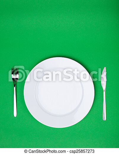 Placa blanca, tenedor y cuchillo sobre fondo verde - csp25857273