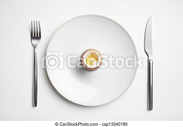 Huevo hervido en el plato con cuchillo y tenedor - csp13340180