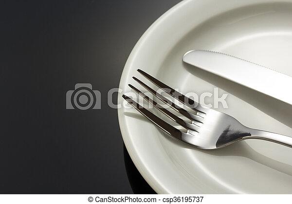 Cuchillo y tenedor en el plato negro - csp36195737