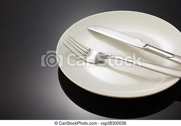 Cuchillo y tenedor en el plato negro - csp38300036