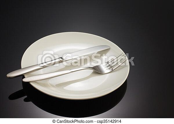 Cuchillo y tenedor en el plato negro - csp35142914