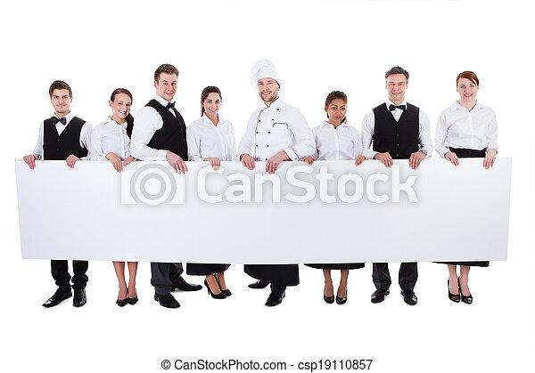 Grupo de personal de catering sosteniendo una bandera en blanco - csp19110857