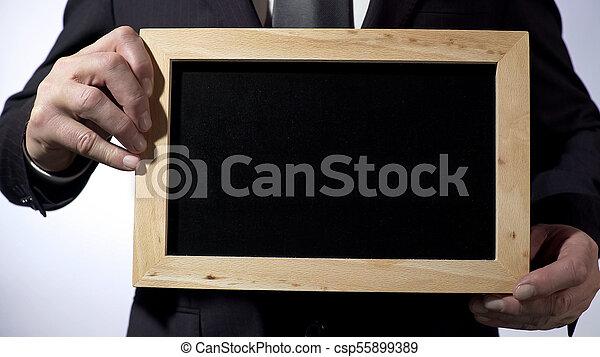 Planta de pizarra con espacio vacío para tu texto, signo de hombre de negocios - csp55899389