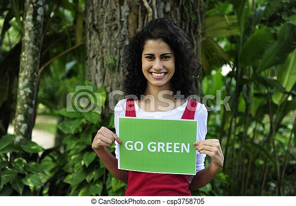 La conservación del medio ambiente: una mujer en el bosque con una señal verde - csp3758705