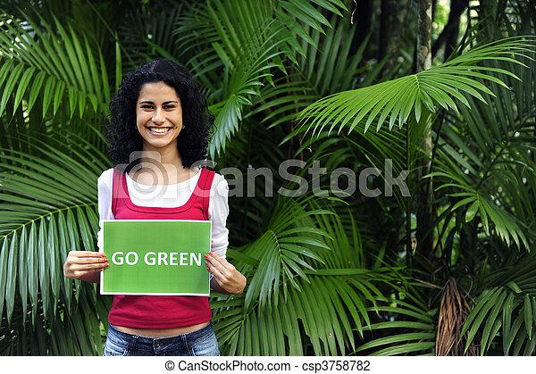 La conservación del medio ambiente: una mujer en el bosque con una señal verde - csp3758782